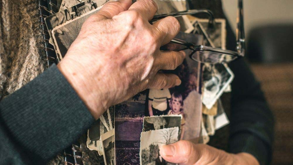 A self-portrait of a woman's hands holding old family photographs