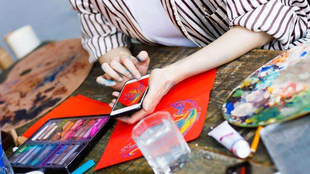 Artist using mobile phone to sell their art online.