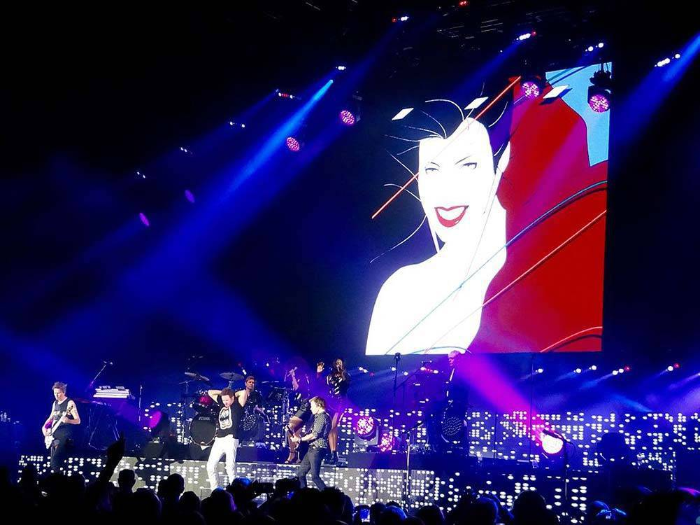 The famous Patrick Nagel image from the album Rio displayed on stage behind the band.