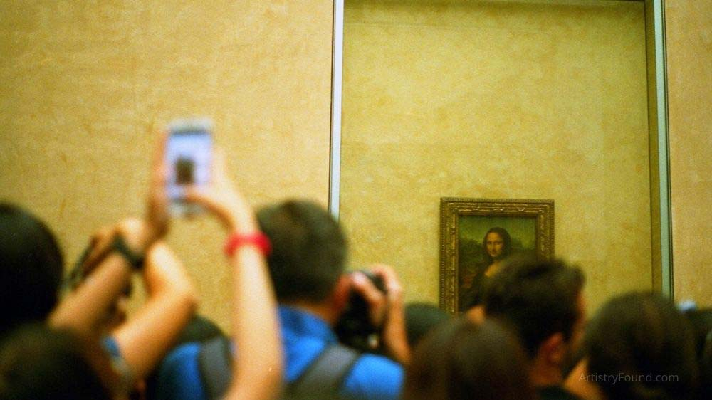 A crowd of camera phone carrying enthusiasts visiting the Mona Lisa.